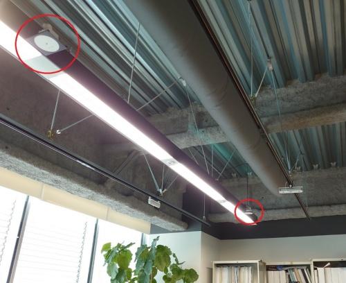 照明1つひとつを制御できる規格「DALI」に対応した照明と、Bluetoothによる無線通信ができる人感センサー(赤い丸印)を組み合わせて、オフィスの照明を個々に制御する(写真:日経クロステック)