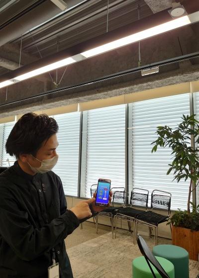 事前に登録した社員であると認証されると、自分のスマートフォンアプリから照明の明るさを自由に調整できるようになる(写真:日経クロステック)