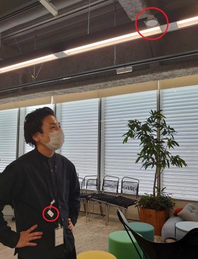 大浦氏がビーコン(小さな赤い丸印)を身に着け、Bluetoothに対応した照明のセンサー(大きな赤い丸印)が個人を特定する(写真:日経クロステック)