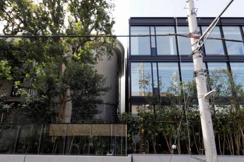 2020年3月に完成した高級分譲マンション「プラウド上原フォレスト」。改修した既存棟(写真左側)と新築したガラス張りの「増築棟」(写真右側)を接続している(写真:竹中工務店)