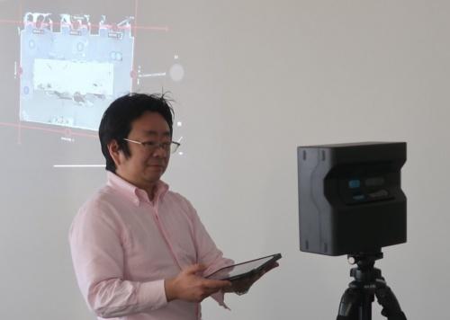 3D赤外線スキャンカメラ「マーターポート」を使った撮影を体験している私(写真:日経クロステック)