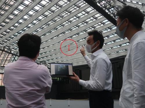 日建設計の設計担当者2人と白い梁を見上げながら、説明を受ける私(左)。中央がファサードエンジニアの村上博昭氏。梁のデプス(上弦材と下弦材の間隔)は最大で1.8mある。写真の赤色矢印の部分(写真:日経クロステック)
