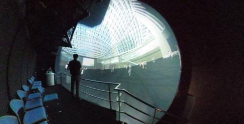 パナソニックの「サイバードーム」に、三角広場のVR(仮想現実)画像を映した様子。広場に立ったときと近い感覚で、ガラスの屋根や梁などを見上げて確認できる(写真:日建設計)