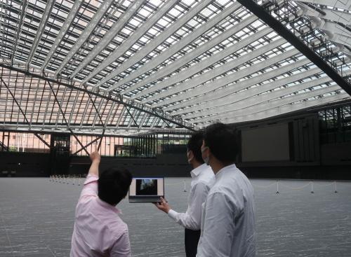 基本・実施設計を手掛けた日建設計の担当者と一緒に三角広場のガラス屋根を見上げながら、日射解析や空調温熱の説明を受ける私(左)(写真:日経クロステック)