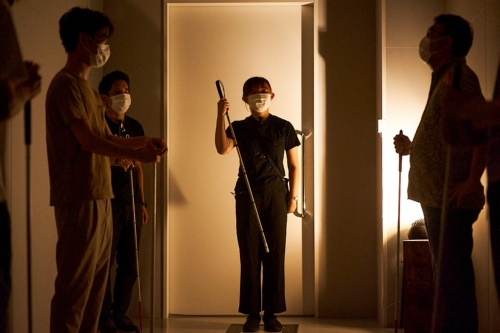 暗闇の案内人である女性スタッフ(中央)。白杖を持ち、参加者に使い方を説明している。彼女は目が見えない(写真:黒羽 政士、提供:echo project)