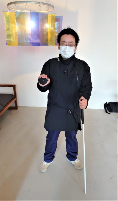 もう片方の手に白杖を持つ。私が着ている服は「echo wear」。ただし今回のプログラムでは、この服は使わない(写真:日経クロステック)