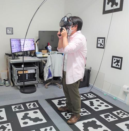 両手で持つMRディスプレーを使い、仮想のガラスを見てみた。床や壁にある白と黒の模様は、現実空間と仮想の画像を正確に重ね合わせるために必要な位置合わせのマーカーだ(写真:日経クロステック)