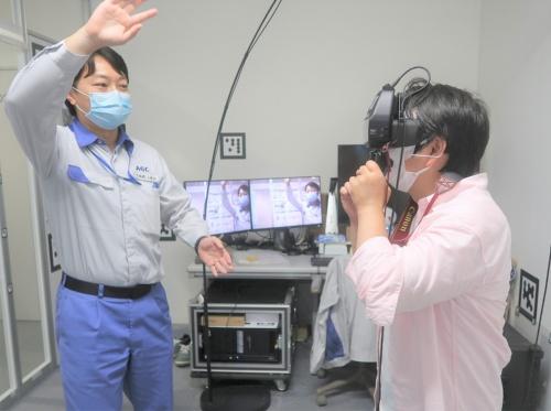 先端基盤研究所の小林光吉マネージャーが、仮想のガラスを手で持つ振りをしてくれた(写真:日経クロステック)