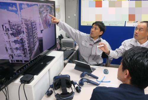作業所長の永井一嘉氏(右)と課長 工事担当の砂川亮馬氏(左)。BIMの画面を見ながら、施工手順などを検討する日々が続いている。手前は今回の建物の設計者。施工で利用するBIMの元データは、設計チームからシステムを介して引き継いでいる(写真:日経アーキテクチュア)
