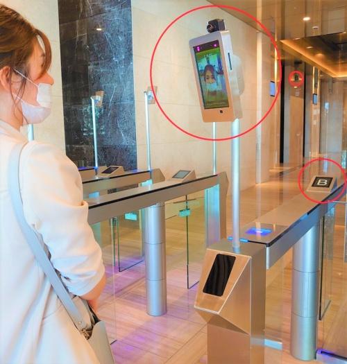 入館ゲートの顔認証カメラ(大きな赤い丸)。登録された従業員の顔情報と一致すればゲートが開く。勤務するフロアに応じて乗るべきエレベーターの番号(小さな赤い丸)が表示されるので迷わないし、人を分散させてエレベーターの混雑を避けられる。この場合は「B」のエレベーターに誘導している。顔認証と同時に検温も実施(写真:日経クロステック)