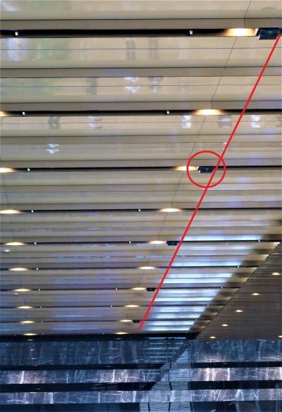 人流を観測するセンサー。地上6階にあるオフィスロビーには、天井にたくさん付いている。斜めの赤い線を引いたラインに沿って付いている黒い箱(赤い丸)は全てセンサー(写真:日経クロステック)