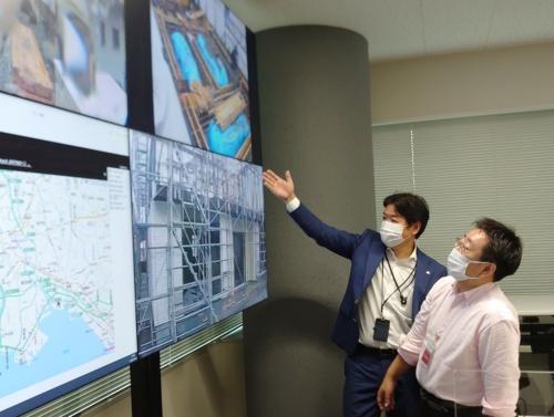 東京本社にある「スマートコントロールセンター」で、施工現場に設置したカメラの映像を見せてもらった。作業の進捗がよく分かる(写真:日経クロステック)