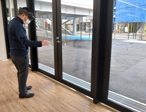 検査担当者が窓サッシの寸法が設計図通りの長さになっているかを確認しているところ(写真:日経クロステック)