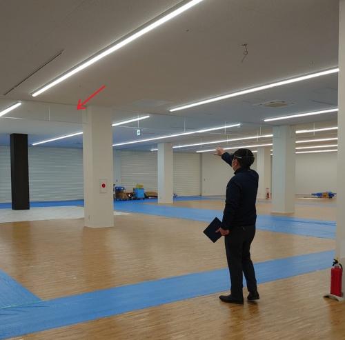 HoloLens 2をかぶり、天井の透明な垂れ壁(赤い矢印)に近づいていく日本ERIの検査担当者(写真:日経クロステック)