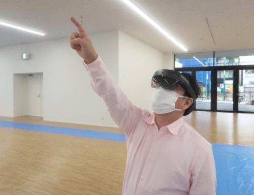 HoloLens 2をかぶった私。検査担当者のまねをして、垂れ壁を指さす(写真:日経クロステック)