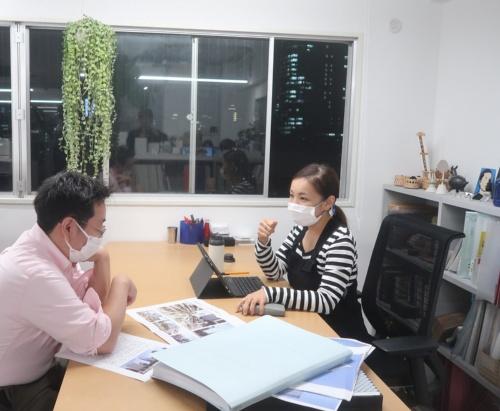 移転したばかりの事務所で永山氏と話す私。オフィス一番奥の隅が永山氏のデスク。だが自分の机に向かっていられる時間は少なく、絶えず動き回っている(写真:日経クロステック)