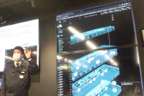 現場にある資機材や担当者の動きを建物のデジタルツイン上に3D表示して管理できるシステム「3D K-Field」の画面をモニターに表示。担当者が手に持っているのがビーコン(写真:日経クロステック)