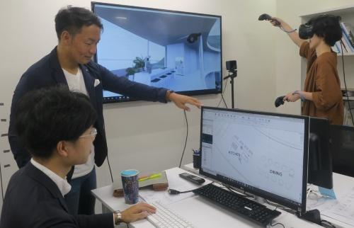 BIMとVRを組み合わせた設計スタイル。左に立つ上司(長澤部長)がBIMを使う設計者(男性)にアドバイスをしているところ。VRのゴーグルをかぶった設計者(女性)は、BIMで変更した部分が3Dの仮想空間でどう違って見えるかを確認している(写真:日経アーキテクチュア)