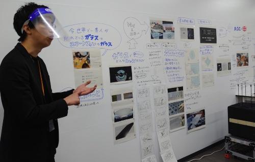 トヨタ自動車のデザイナーが、AGCの協創空間で共同研究している内容をプレゼンテーションする様子。壁中に議論の経過を張り出している(写真:日経クロステック)