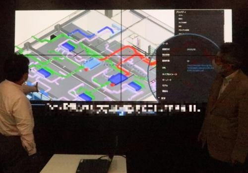 BIM画面をスクリーンに映しながら、越前氏に仮想GPUとVDIの説明を受ける私(左)(写真:日経クロステック)