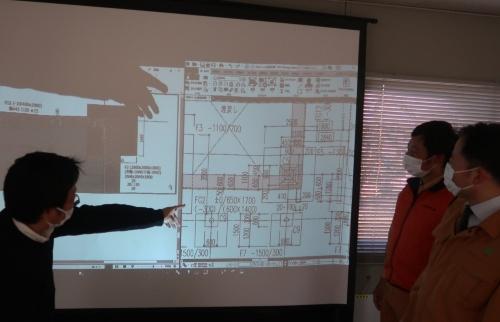 これまでの施工図(写真のスライド右)にはあらゆる数字が盛り込まれており、見間違えることがあった。右手前が藤嶋副課長、右奥が岩村主任(写真:日経クロステック)