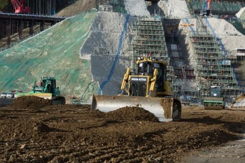 クワッドアクセルを実現場に導入した福岡県朝倉市内での小石原川ダム本体建設工事の施工状況。自動ブルドーザーがコア材をまき出し、その後を追いかけるように後方の自動振動ローラーが転圧を行っている。2018年11月に撮影(写真:大村 拓也)