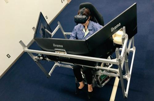 図2 無人化施工VR技術で建設機械を遠隔地で操作する様子(写真:熊谷組)