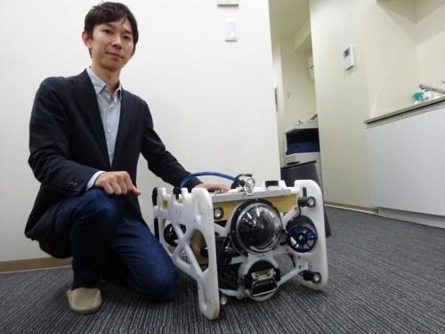 フルデプスの伊藤昌平社長と、水中ドローンの「DiveUnit300」。もともと「深海魚とロボットが好き」という伊藤社長の趣味が高じて開発を始めた。大学在学中から試作機の開発に従事し、2014年に会社設立。初めて造った水中ドローンは深さ1000mまでの潜水に成功した(写真:日経コンストラクション)