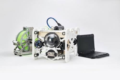 開発した「DiveUnit300」と専用の光ファイバーのケーブル、処理用のパソコン。機体は1台数百万円となる見込みで、販売の他にレンタルも実施する。ケーブルは独自技術で水と同じ比重を実現。浮きも沈みもしないので、水中ドローンの動作の邪魔にならない。耐久性が高い高強度繊維を採用した。1.5kmの長さで約20kgと軽く、持ち運びが容易だ(写真:フルデプス)