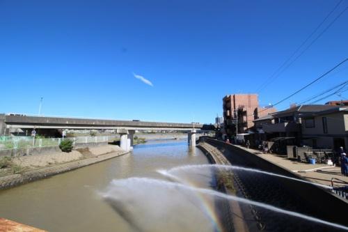 多摩川水系である平瀬川の多摩川への合流地点付近。写真右手の住宅街にあった浸水区域からポンプアップして放水している様子。10月13日撮影(写真:日経 xTECH)