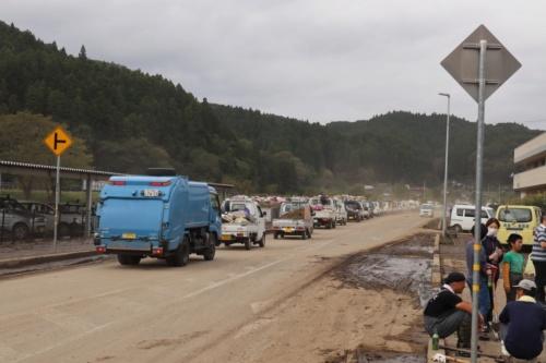 大子町役場の裏に設けたゴミ置き場にはトラックの長蛇の列ができていた。乾燥した泥が砂ぼこりとなって舞うため、マスクをして復旧作業をする住民が多い。2019年10月14日午前11時ごろ撮影(写真:日経 xTECH)