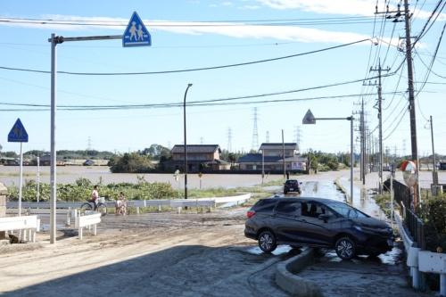 水が引いた場所には、前面の壊れた乗用車が縁石ブロックに乗り上げるように残されていた。10月13日午後2時ごろ撮影(写真:日経 xTECH)