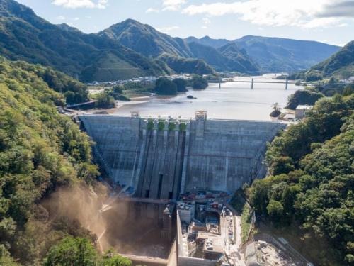 台風19号が通過した後の10月13日午後2時に撮影した八ツ場ダム。利水放流管から泥混じりの水が噴き出し、土煙を上げる。堤体上空でのドローン飛行は許可が必要なため、許可が不要なダム下流の吾妻峡からドローンを離着陸させて撮影した(写真:大村 拓也)