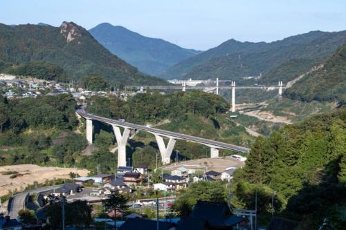 右岸の高台から丸岩大橋を見下ろす。写真奥に不動大橋と八ツ場大橋、ダム堤体が見える。10月10日撮影(写真:大村 拓也)