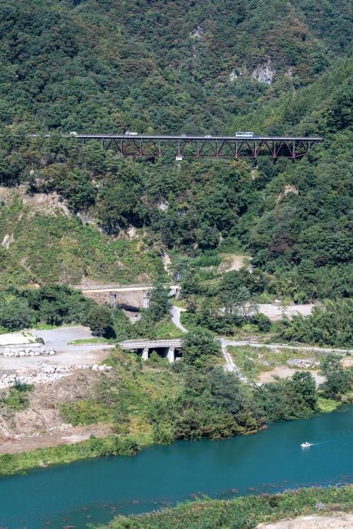 山の中腹に架かるトラス橋は付け替え国道145号。下側に架かる2本の橋は旧JR吾妻線と旧国道145号。湛水によって水位が上昇した吾妻川を調査用のボートが通った。不動大橋付近から10月10日撮影(写真:大村 拓也)