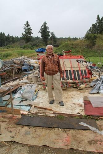 飛散したビニールハウスの前で、竜巻が通過した時の様子を語る大橋安夫氏(写真:日経 xTECH)