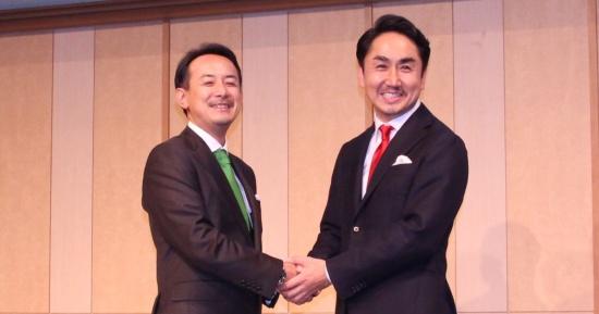 記者会見で握手するZホールディングスの川辺健太郎社長(左)とLINEの出沢剛社長