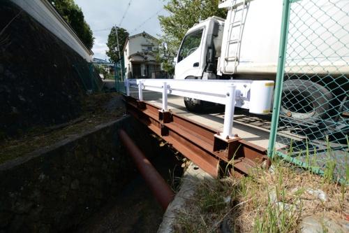 写真1■ 通行止めからわずか1カ月で架け替えた仮設橋。現在もゴミ収集車や乗用車が通っている(写真:日経コンストラクション)
