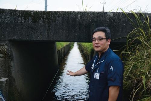 写真1■ 熊本県玉名市が管理する道路橋の前にいるのは、建設部土木課橋梁メンテナンス係の木下義昭係長。同市には、用排水路をまたぐ橋が多い(写真:日経コンストラクション)