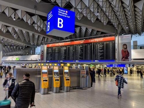 """ドイツのフランクフルト国際空港。「I am digital」のキャッチコピーが躍る広告横の航空便案内表示は、昔懐かしの""""パタパタ""""とフラップ表示が切り替わるアナログ方式のもの"""