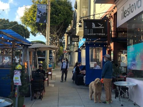 米国カリフォルニア州サンフランシスコの目抜き通り。同州は6月15日に新型コロナ禍対策の全ての制限を解除し、経済の全面再開を宣言。少しずつ以前のにぎわいを取り戻しつつある
