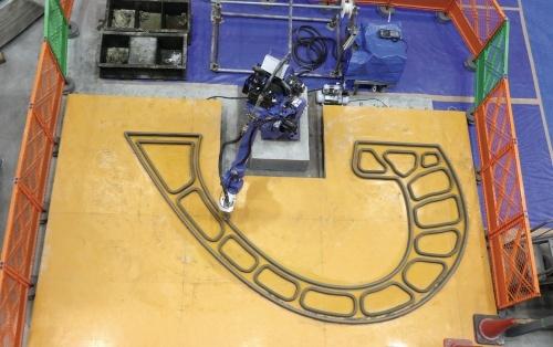 写真1■ベンチの部材を製造する大林組の3Dプリンター。セメント系材料を用いて国内最大規模の構造物を製造できる。ベンチの部材はロボットアームの腕が届く最大範囲で設計した。ロボット自体をレール上で動かせるようにすれば、さらに大型の部材も製造できる(写真:日経アーキテクチュア)