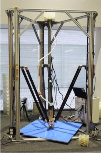 写真1■竹中工務店と慶応義塾大学の田中浩也教授が共同で開発した3Dプリンター「ArchiFAB」。中央の黒いロッドでエクストルーダーを動かしながら樹脂を押し出して積層し、型枠をつくる。最大で1辺が90cm程度の部材を製作できる(写真:竹中工務店)