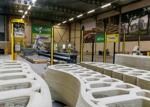 写真2■ 大型構造物の製造に特化した建設用3Dプリンター工場。写真奥のサイロからポンプでモルタルをロボットアーム先端のノズルに送る(写真:BAM Infra)