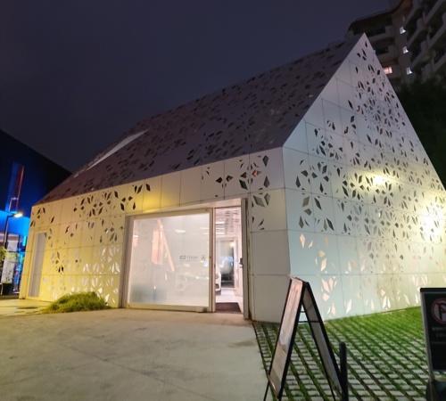 夜が更けた時間帯のEQ House。照明が輝き、パネルの模様がよく見える。家の中にはクルマが止まっている(写真:日経アーキテクチュア)