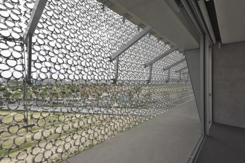 ACADEMIC-ARKの2階から5階までをステンレス鋳物のスクリーンが覆う。スラブから持ち出したブラケットで、パネル状に分割したスクリーンを支持している(写真:生田 将人)