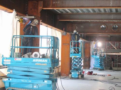 鹿島スマート生産ビジョンのパイロット現場「名古屋伏見Kスクエア」で本格適用した溶接ロボット。柱と梁(はり)の仕口部の下フランジ全585カ所を、ロボットが上向き溶接した。高所作業車を用いた下方からの上向き溶接が可能になったことで、上階では床施工が並行できるメリットもあった。鹿島では現在、大型の鉄骨柱にも対応できる新型の現場溶接ロボットの開発も進めている(写真:鹿島)
