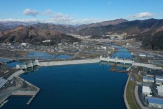 岩手県大槌町の空撮写真。手前に見える大槌湾と2本の大槌川・小槌川とに挟まれた部分に、大槌町の中心市街地があった。上の写真は東日本大震災前の2003年4月、真ん中は震災後の11年4月時点。20年1月の空撮写真(下)では、2つの水門と防潮堤が見える(写真:安藤ハザマ・植木組・伊藤組土建・南建設JV)
