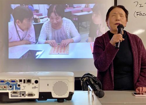 特別講師の角田まき子氏は初めて講座に参加した際、実際にiPadのアプリを操作する前に、段ボールで作られた教材を指で触ってiPadの形やアプリの位置などを学んだことを紹介