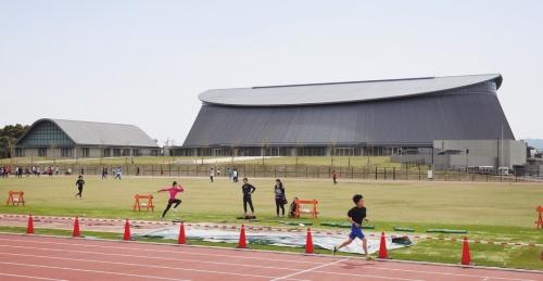 北東から見た「静岡県草薙総合運動場体育館」(2015年)の全景。右手にメインフロア、左の小さな建物にサブフロアが入る。外装は亜鉛合金板の折板ぶきと縦ハゼぶき(写真:吉田 誠)